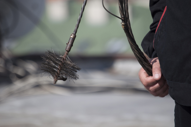 Chimney sweep at work, Close up of the hand holding a chain with the broom to clean the chimney